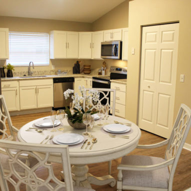 Round white dining table and chairs with kitchen in the background.