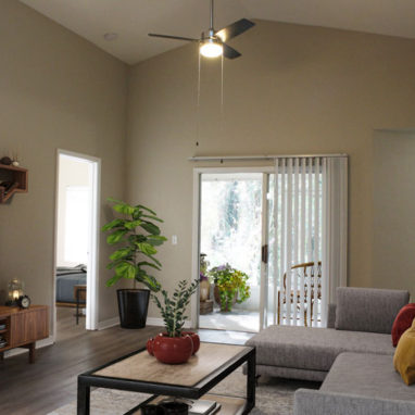 A furnished living room with vaulted ceilings and a glass door leading out to a patio.